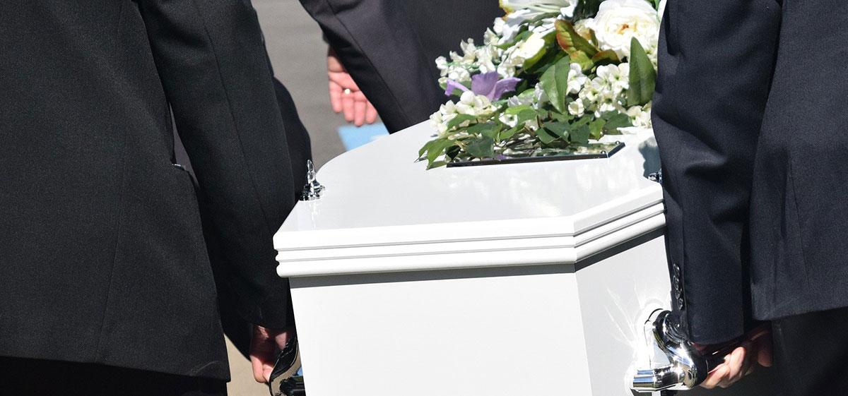 cercueil blanc emmené par des porteurs funérailles